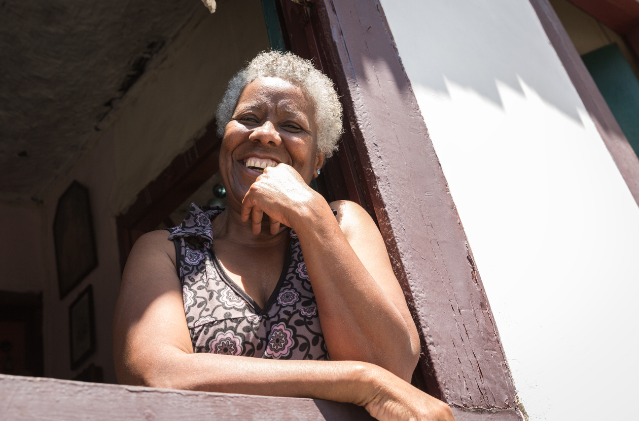 older woman smiles out her window